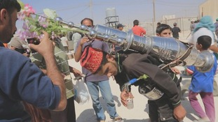 A street vendor pours a cup of coffee from a flask on his back at Zaatari refugee camp in Jordan