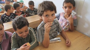 Children eating fig rolls at school in the camp