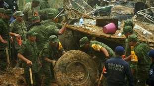 Soldiers and police work around the wreckage of a bus after it was buried by a mountain landslide at Altotonga, Veracruz state