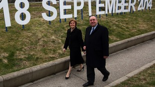 Scottish First Minister Alex Salmond and Deputy First Minister Nicola Sturgeon walk past a sign showing the date for the referendum