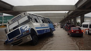 A stranded bus is seen as cars make their way through a flooded street in Acapulco.