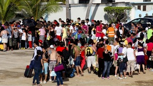 People stand in line while waiting to be airlifted by Mexico's Secretariat of National Defense out of Acapulco yesterday.