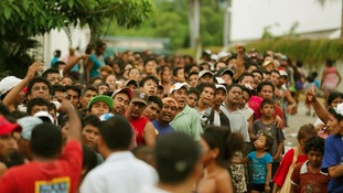 People queue to receive food rations on a flooded beach in Acapulco.