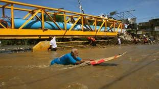A man uses a surfboard to cross a flooded street in Acapulco.