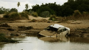 A car lies partially submerged in floodwater on a golf course at a Acapulco hotel.