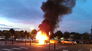 Smoke rises into the air after from a car on fire in a supermarket car park in Banbury