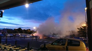 Smoke billows across the car park at a supermarket in Banbury from a car on fire