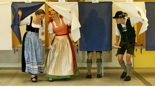 Voters Veronika Stuerzer, Monika Merk, Johann Merk and Michael Merk (L-R) wearing traditional Bavarian costume cast their ballots