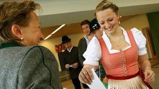 Voter Monika Merk, wearing a traditional Bavarian Dirndl, casts her ballot