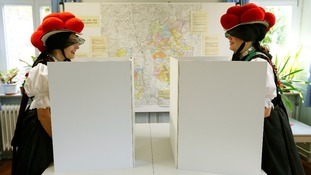 Corinna Woehrle and Gerlinde Moser (L) wearing traditional Black Forest costumes, fill ballots