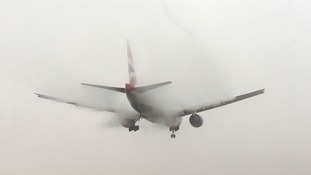 A British Airways planes lands in the fog at Heathrow Airport, London, this morning.