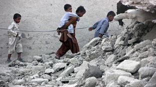 Survivors of an earthquake walk on rubble of a mud house after it collapsed following the quake.