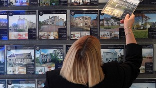 A woman looks at houses for sale in an estate agents.