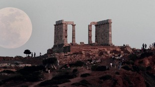 A full moon rises behind the Temple of Poseidon in Cape Sounion, south east of Athens, Greece,