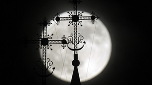 The full moon rises behind a steeple with crosses of an Orthodox church in the town of Novogrudok,  west of Minsk, Belarus