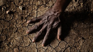 A man places his hand on the parched soil in the Greater Upper Nile region of northeastern South Sudan