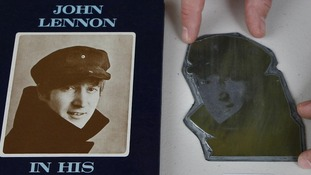 Auctioneer Paul Fairweather positions an image on a printers plate of John Lennon