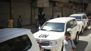 A convoy of UN vehicles is seen driving through the streets of Damascus on August 26.