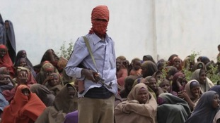 An al-Shabaab fighter stands over women at a food distribution camp in Shebelle, Somalia, in 2011. MSF left the country last month.