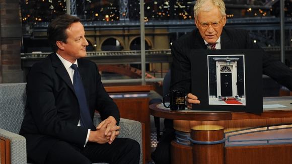David Cameron looks on as David Letterman holds up a picture of Larry the cat sitting on red carpet outside the Prime Minister's home.