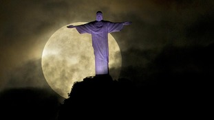 "A ""supermoon"" is seen behind the Christ the Redeemer statue in Rio de Janeiro"