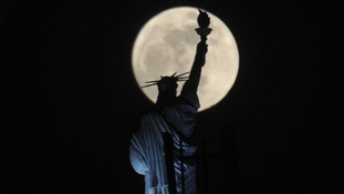 The full moon rises behind Statue of Liberty replica atop of a hotel in Kosovo's capital Pristina last night