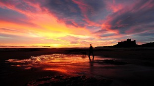 A man walks his dog at sun rise near to Bamburgh Castle in Northumberland.