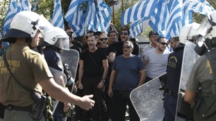 Supporters of extreme-right Golden Dawn party shout slogans outside the Greek police headquarters in Athens