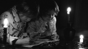 Image from 1977 of two children with candles in a blackout.