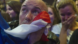 A supporter of outgoing French President Nicolas Sarkozy's covers his face with the national flag
