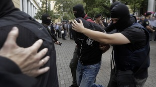 A member of the far-right Golden Dawn party is escorted by anti-terrorism police officers to court in balaclavas.