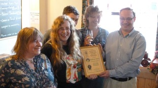 Ian Pinches (far right) and his wife Lesley-Ann being presented with their award from CAMRA