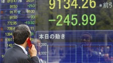 A man speaks on a mobile phone in front of a securities firm's electronic stock board in Tokyo