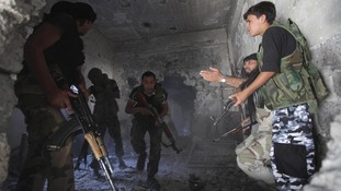 A Free Syrian Army Commander takes cover during a gun battle.