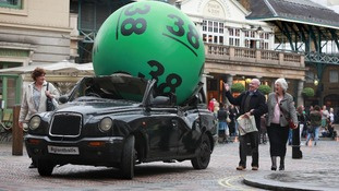 A giant Lotto ball appears to have landed on a London taxi in Covent Garden, London as part of the launch of a new National Lottery.