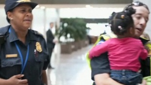 A young girl is carried from the area by security officials