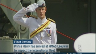 Prince Harry salutes at the HMAS Leeuwin to inspect the international fleet.