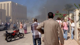 Residents and tourists watch smoke rising near a state security building in South Sinai.