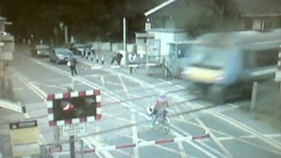 CCTV pictures show the cyclist with the fast moving train approaching