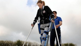 How do 'bionic legs' help paralysed Claire to walk?