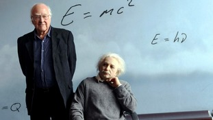 Peter Higgs posing next to a sculpture of Albert Einstein at the CosmoCaixa science museum in Barcelona.