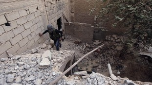 A Free Syrian Army fighter carries his weapon as he walks on the rubble of a damaged building in Deir al-Zor.