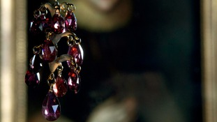 A garnet pendant hangs on display in front of a portrait of Elizabeth Wriothesley, Countess of Southampton