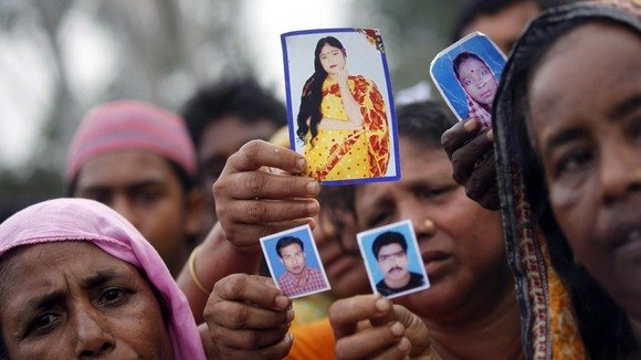 Relative show pictures of garment workers who are missing