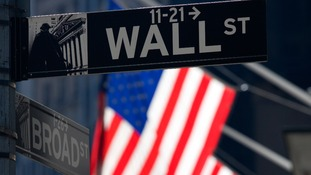 The sign for Wall Street with Stars and Stripes behind.