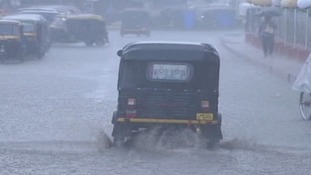 An auto rickshaw drives through a flooded street in eastern India