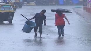 Residents walk through a flooded street