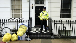 A police officer stands guard outside the home of Gareth Williams.