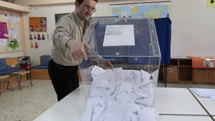 A judicial representative empties a ballot box after the end of voting at a polling station in Athens.