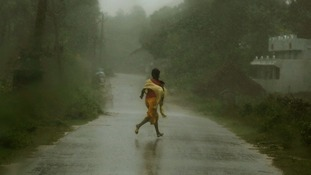 A girl runs for shelter in heavy rain brought by Cyclone Phailin in Ichapuram town in Srikakulam district.